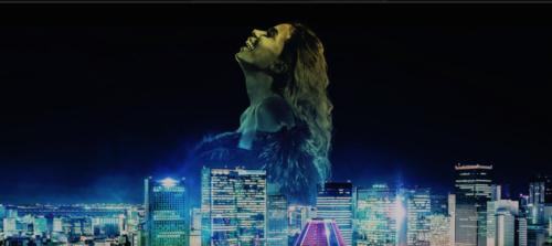 Imagem com a cantora Anitta ao fundo de uma cidade virtual