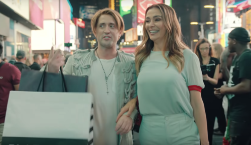 Foto dos atores um home e uma mulher com sacola de compras em uma calçada movimentada
